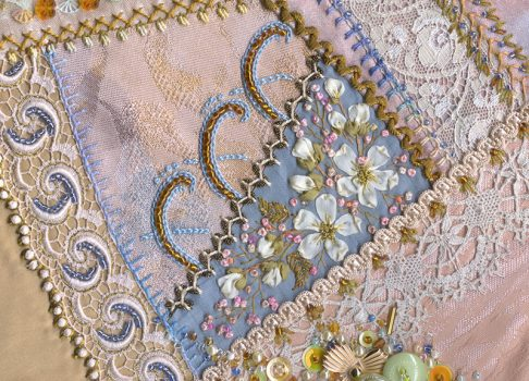A pink crazy quilt block completed for the stitch sampler quilt