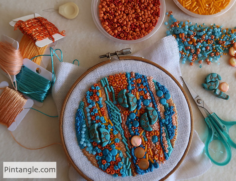 stitchers table showing beads threads and hoop embroidery